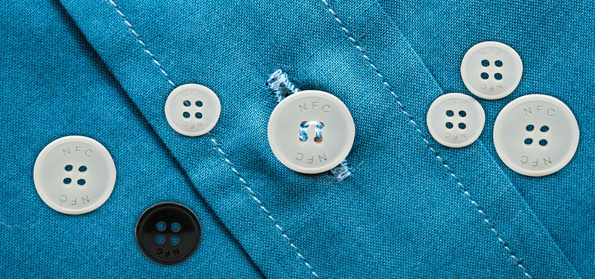 NFC buttons sewn on blue shirt